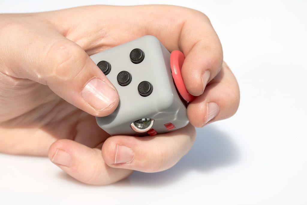 Dłoń bawiąca się Fidget Cube